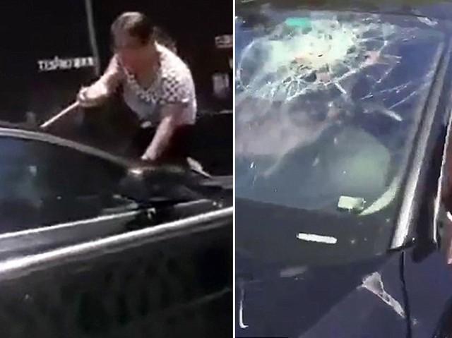 Trong lúc gào thét bắt cô bồ của chồng ra khỏi xe, người vợ không kiềm chế được đã dùng gậy đập nhiều phát vào kính chắn gió. Ảnh: Asiawire.