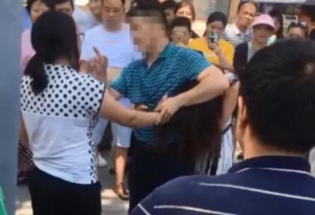Vợ túm tóc lôi tình địch ra khỏi xe nhưng cô nhân tình được người chồng che chở, bênh vực. Ảnh: Asiawire.