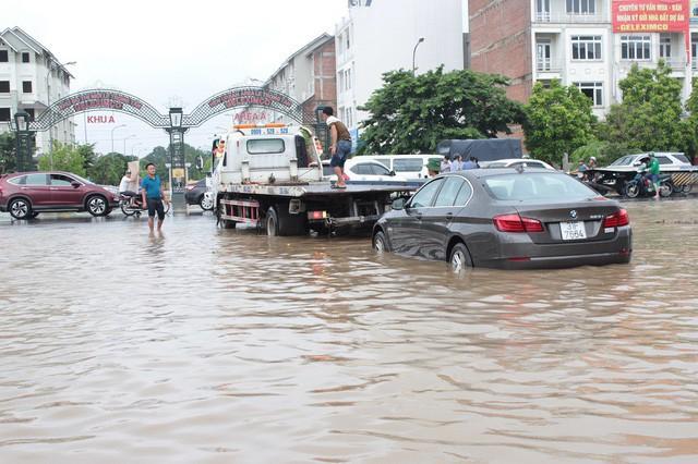 Một xe ô tô mắc kẹt trong biển nước phải thuê xe cứu hộ kéo qua điểm ngập.