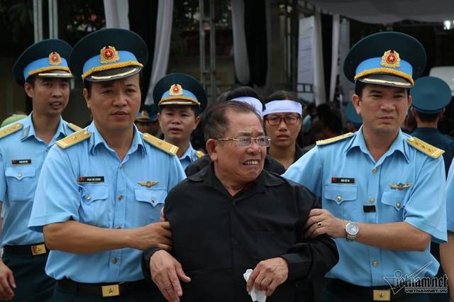 Thân phụ phi công Phạm Giang Nam được các cán bộ chiến sĩ dìu lên xe để đưa con về quê nhà. Ảnh: Vietnamnet