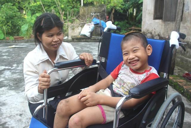 Cháu Dương thích thú bên chiếc xe lăn được Hương (Ngân hàng SHB) trao tặng. Ảnh: Đ.Tùy