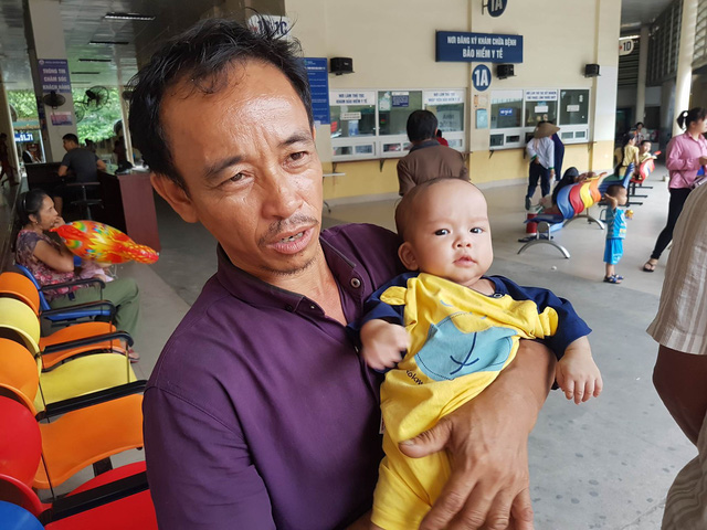 Bé Đinh Văn Đại trong vòng tay cha, bên hành lang Bệnh viện Nhi Trung ương.     Ảnh: B.Loan