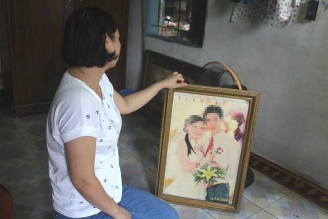 Chị H. bên chiếc ảnh cưới 10 năm trước giữa chị và anh T. vẫn được để trong gian nhà sinh sống của 2 vợ chồng. Ảnh: Đ.Tùy