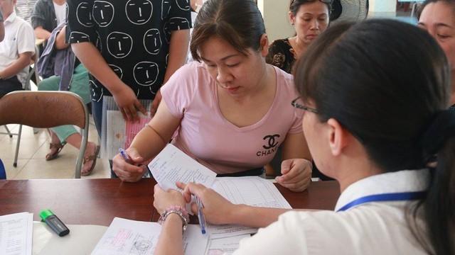 Phụ huynh rút hồ sơ để nộp vào một trường công lập hạ điểm chuẩn ngày 5/7. Ảnh: Thanh Hùng.