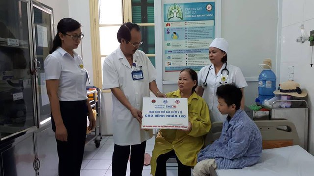 TS Vũ Xuân Phú, Phó Giám đốc BV Phổi Trung ương đại diện Quỹ PASTB trao bản tượng trưng hỗ trợ thẻ BHYT cho gia đình nhà em Nghĩa. Ảnh PT
