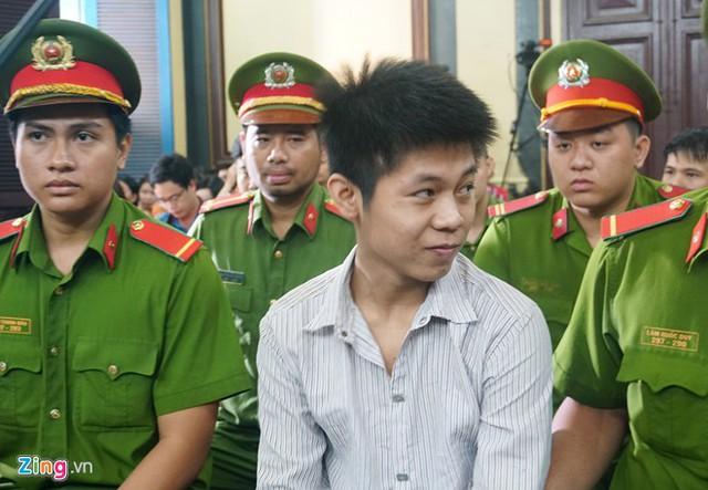 Bị cáo Tình mỉm cười trước khi bắt đầu phiên tòa sáng 9/7. Ành: Lê Quân.