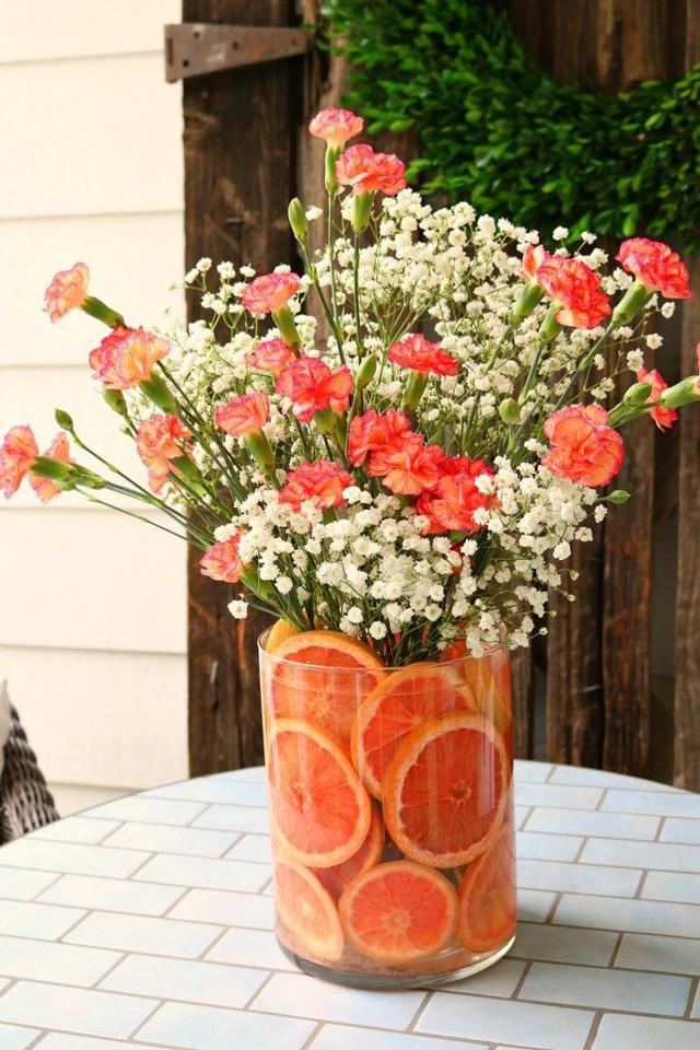 Sử dụng những bông hoa màu cam cùng sắc màu với những lát cam vàng óng là cách bài trí cắm hoa vừa xinh vừa lạ. Điểm thêm những bông hoa nhỏ màu trắng sẽ khiến lọ hoa trông thật ấn tượng.