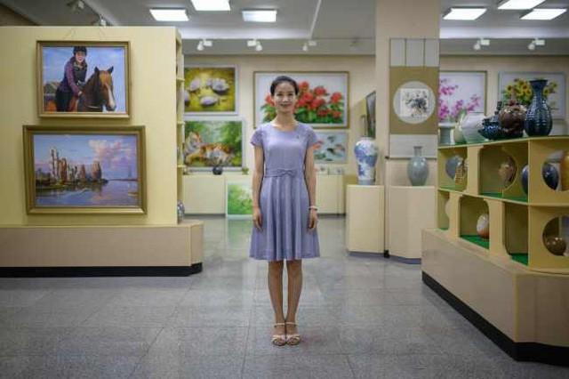 Nhân viên bán hàng Park Um-hyang, 24 tuổi, tại một cửa hiệu của trung tâm nghệ thuật Mansudae (MAS) tại Bình Nhưỡng ngày 25/7. Nhà cố lãnh đạo Kim Nhật Thành là người thành lập nên MAS vào năm 1959. Trung tâm này có khoảng 700 nghệ sĩ hoạt động trong một khu tổ hợp có kích thước ngang bằng một ngôi làng nhỏ, được chia ra hàng trăm khu nghệ thuật khác nhau.