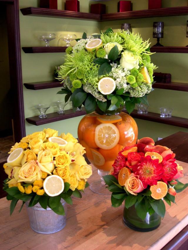 Không chỉ ở dưới đáy lọ, bạn có thể bổ sung những trái cây cam chanh lên xung quanh điểm tô vẻ đẹp của hoa.