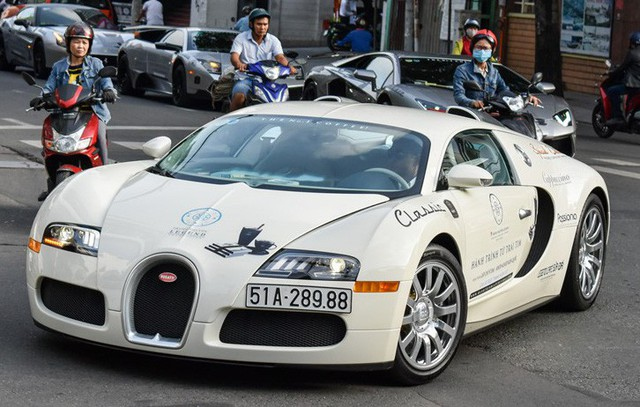 Siêu xe Bugatti Veyron độc nhất Việt Nam. Siêu xe này được đưa về bởi đại gia Minh Nhựa vào năm 2012, và về tay ông chủ cà phê Trung Nguyên hồi cuối tháng 5 vừa qua nhằm chuẩn bị cho chuyến hành trình lần này. Chiếc Bugatti Veyron có màu sơn gốc là đỏ-trắng, nhưng đã dán lại decal màu trắng hoàn toàn, do ông Đặng Lê Nguyên Vũ có sở thích dán màu trắng và màu xám cho dàn siêu xe. Ảnh: Zing.