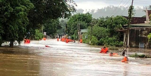 Các chiến sĩ công an huyện Quỳ Hợp ngâm mình trong nước để vào các điểm ngập nước giúp người dân.