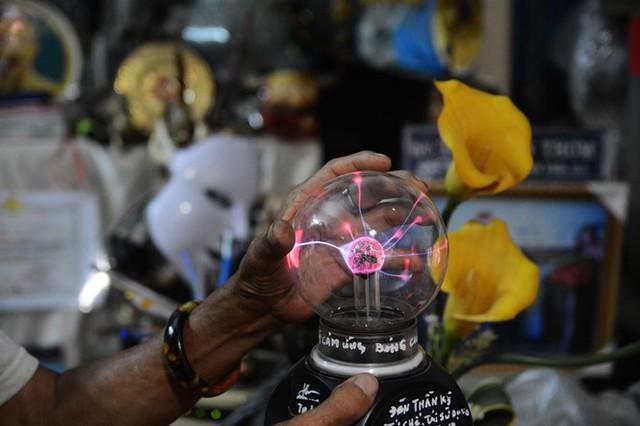 Một trong những sản phẩm tái chế lạ lùng nhất của ông là chiếc đèn cảm ứng. Đế đèn được lấy từ đèn sạc, kết hợp linh kiện của ti vi. Chóa đèn là bóng cao áp, bên trong là giấy bạc. Tất cả đều được ông nhặt về khi đi gom rác. Khi bạn chạm tay vào, chiếc đèn sẽ búng ra những tia sáng cực kỳ đẹp mắt và chuyển động khi ngón tay bạn di chuyển. Ảnh: Hoài Nhân