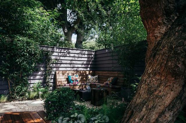 Góc vườn bên ngoài xanh mát với cây cổ thụ rợp bóng. Chủ nhân đã thiết kế thêm ghế góc bằng gỗ với những chiếc gối tựa nhiều màu sắc để tạo nên góc thư giãn ngoài trời bình yên, trong lành.