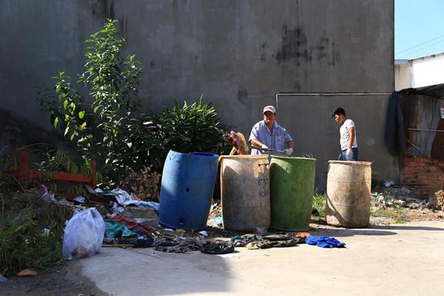 Lực lượng chức năng tìm thi thể nạn nhân ở các thùng rác. Ảnh: Ngọc An.