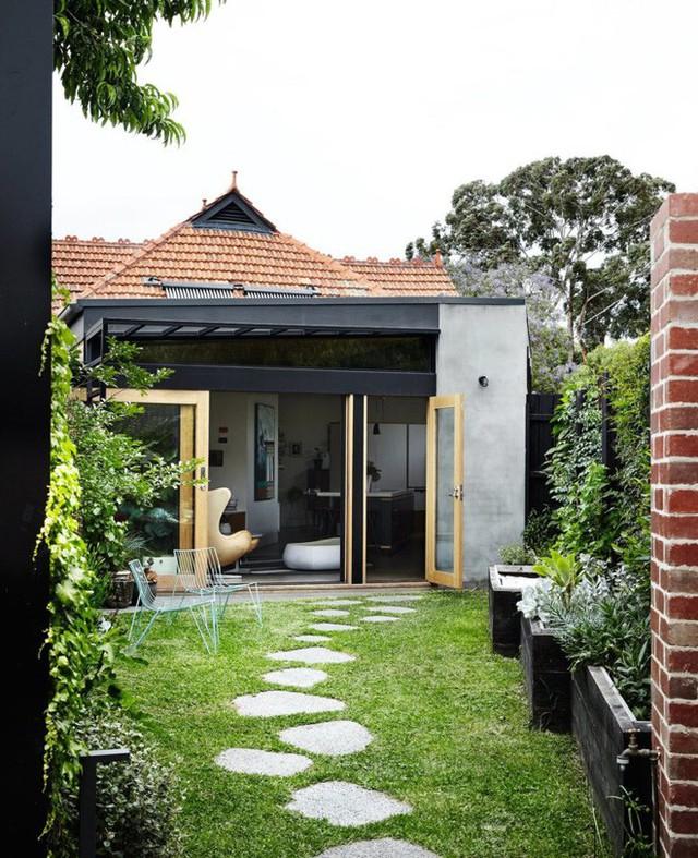 Từ cổng vào nhà, lối vào được trồng cỏ xanh tươi một màu, đá được ốp làm lối đi đẹp như một bài thơ. Hai bên hàng rào được thiết kế vườn đứng vô cùng ấn tượng. Vẻ đẹp xanh tươi của cây cỏ, nét bình yên của lối đi dịu dàng giúp mọi người thêm yêu hơn không gian giản dị này.
