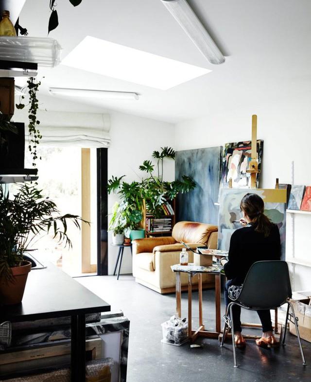 Phòng khách đồng thời là phòng vẽ của cặp vợ chồng trẻ. Cách sắp xếp vô cùng ngẫu hứng với các khu vực chức năng cần thiết theo nhu cầu sử dụng. Chiếc ghế sofa đơn vừa là nơi chuyện trò, đọc sách vừa là nơi để tận hưởng khoảng xanh trong nắng vàng bên ngoài hiên nhà. Góc bên cạnh được đặt giá vẽ và kệ treo tranh. Những sắc màu ấm cúng từ nội thất và tranh vẽ tạo nên không gian vô cùng ấn tượng và đặc sắc.