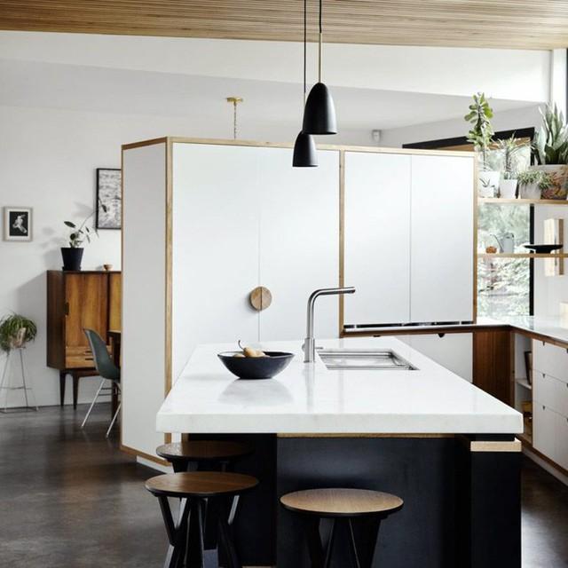 Nhà bếp màu trắng tinh khôi đủ để mọi người cảm thấy yêu hơn chốn đi về của mình. Toàn bộ nội thất chủ yếu được sử dụng chất liệu gỗ pha nhựa công nghiệp. Không gian trắng giúp căn phòng vốn nhỏ hẹp trở nên rộng thoáng bất ngờ.