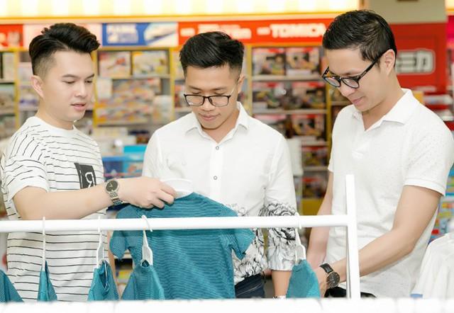 Ca sĩ Nam Cường (trái) và MC Quốc Bình (giữa) chọn trang phục cho con. MC Anh Quân thích thú ngắm nghía những bộ đồ xinh xắn.