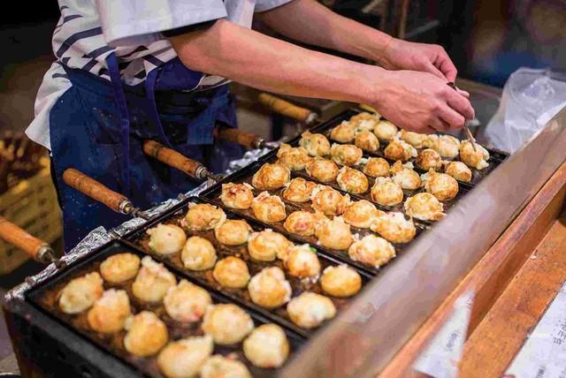 Takoyaki: Được gọi nôm na là những quả bóng bạch tuộc, món ăn này có hành lá, gừng ngâm, bột chiên giòn tenkasu, rong biển và những miếng bạch tuộc nhỏ. Phần topping ăn kèm tương tự món okonomiyaki, song takoyaki nóng chảy bên trong, vì vậy bạn cần chú ý để tránh bỏng lưỡi khi cắn vào. Ảnh: Intrepid Travel.