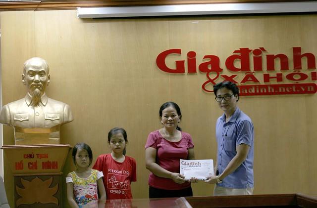Phó TBT Báo Gia đình và Xã hội Nguyễn Chí Long trao tiền cho gia đình bà Hồng. Ảnh Chí Cường