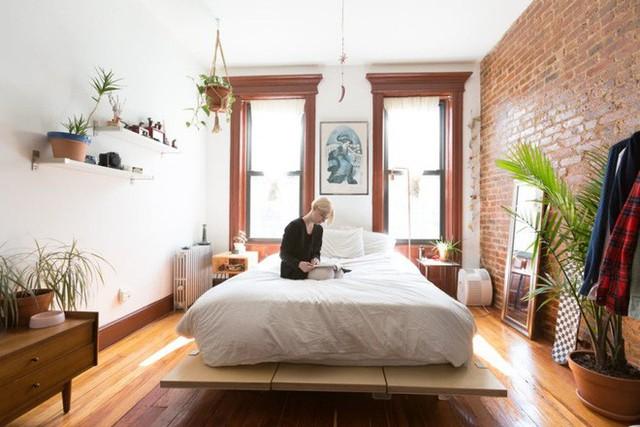 Không gian chính của căn hộ vô được cô gái đưa ra giải pháp sử dụng thành khu vực nghỉ ngơi. Với chức năng cơ bản và cần thiết, căn phòng được ốp sàn gỗ, đóng giường bằng những thanh gỗ ghép. Hơn hết, căn phòng đẹp và gọn khi có tủ đựng đồ nho nhỏ kèm giá treo đồ tiện ích. Thêm vài điểm nhấn ấn tượng từ gương, cây xanh và tranh treo trên tường.