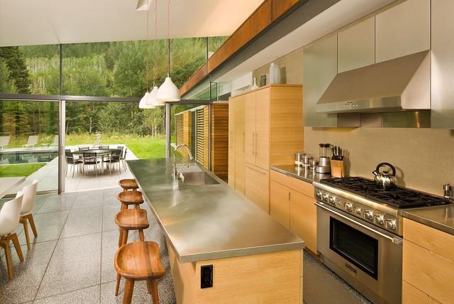 Nhà bếp bằng gỗ và kim loại nhìn ra hồ bơi bên ngoài.