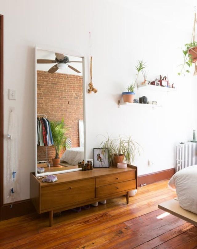 Đối diện với giường ngủ là khu vực đặt gương kèm tủ đựng đồ. Thêm tranh, thêm chậu cây hay vật dụng lưu niệm được sắp xếp khéo léo trên tường, căn phòng như thêm vẻ đẹp bình yên và lãng mạn.
