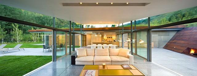 Khu vực tiếp khách theo phong cách Pavilion được bao quanh bởi các bức tường kính và cửa kính trượt.