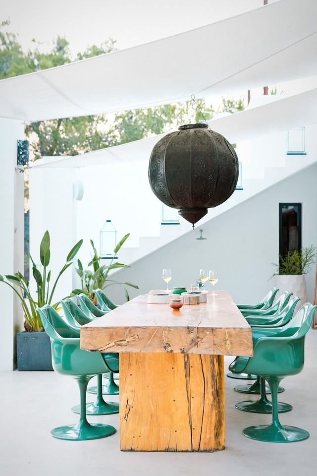 Không gian ăn uống ngoài trời cực thời trang với bàn gỗ thô và ghế nhựa kiểu dáng đẹp màu ngọc lam.