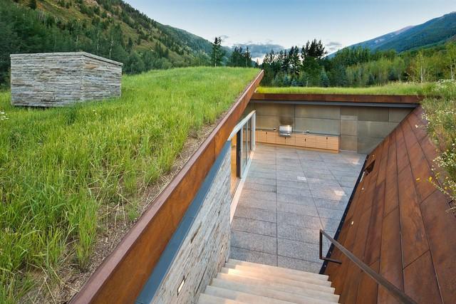 Không gian ngoài trời được bao quanh bởi những bức tường phủ vỏ.Hồ bơi và ngôi nhà được cung cấp chủ yếu bằng năng lượng mặt trời.