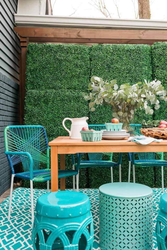 Bàn gỗ trung tính và ghế màu ngọc lam rực rỡ bao phủ một không gian hiện đại.