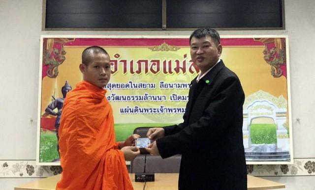 Huấn luyện viên Ekapol (trái) nhận tấm thẻ căn cước từ lãnh đạo huyện Mae Sai hôm 8/8. Ảnh: AP.