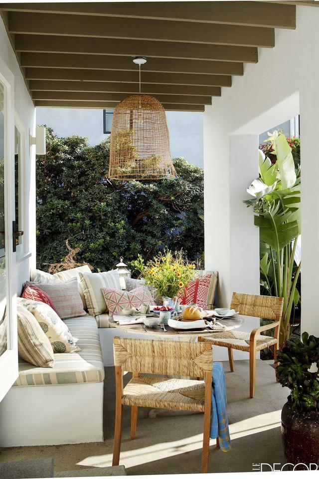 Ngôi nhà có một mái hiên tắm nắng lớn với các ghế ngồi êm ái và ghế mây mộc mạc. Vải từ Kathryn, bàn là từ bộ sưu tập của Pháp - Finds và những chiếc ghế từ Consort.