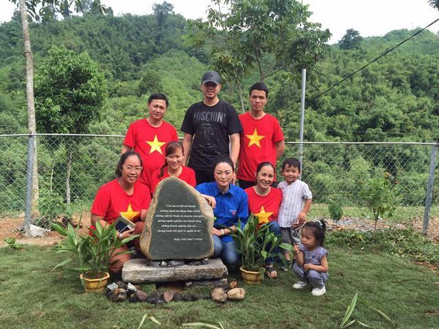 Bà Văn Thùy Dương (áo xanh) bên hòn đá khắc câu nói của cha mình