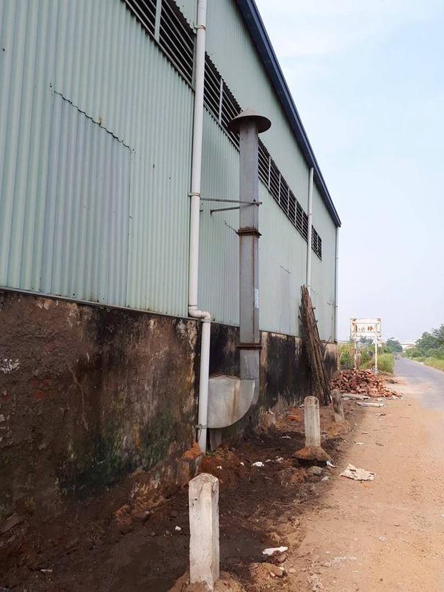 Ống xả thải của một trong những nhà xưởng nơi đây đặt sát đường đi, cao chỉ tầm 2m. Ảnh: Huyền Chi