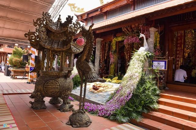 Cổng vào điện chính được danh hài Hoài Linh trang trí cầu kỳ. Bên lư đồng, chim hạc, hai bên lối vào điện còn có chim công được kết từ hoa lan.