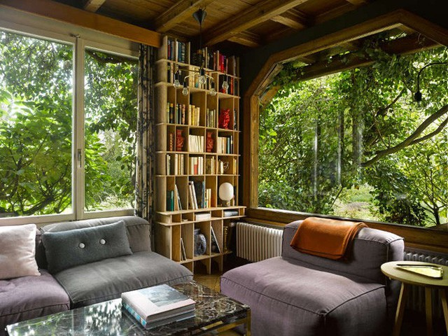 Phòng khách với những ô cửa kính rộng mở đón nắng gió và in bóng cây xanh. Góc phòng được bố trí kệ đựng sách. Những sofa được ghép êm ái giúp mọi người thoải mái tận hưởng cuộc sống chậm rãi, bình yên.