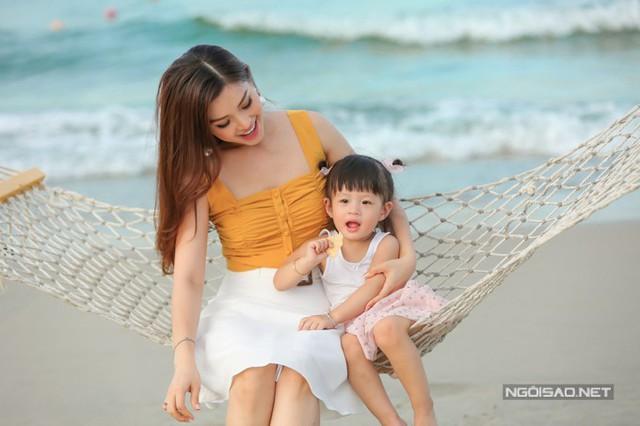 Hai mẹ con vui đùa cùng nhau trước biển.