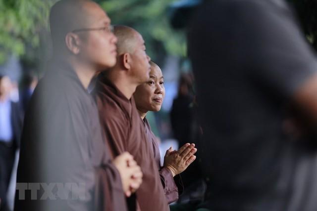Những nhà sư được mời đến làm nghi lễ nhà Phật tại Lễ tang không ngừng đọc kinh. (Nguồn: TTXVN)
