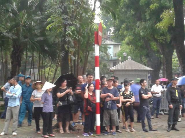 Mặc dù trời mưa nhưng nhiều người dân đứng trước Nhà tang lễ Quốc gia chờ đưa tiễn Chủ tịch nước Trần Đại Quang. Ảnh: Ngọc Tuấn