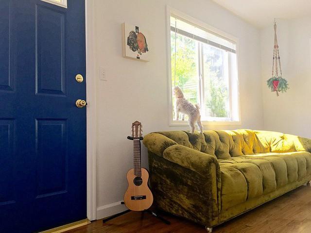 Cửa chính ra vào được cô gái sơn màu xanh đậm. Màu xanh dương đậm này kết hợp với ghế màu xanh lá pha ghi giúp không gian đẹp mệ mẩn, hiện đại và duyên dáng.
