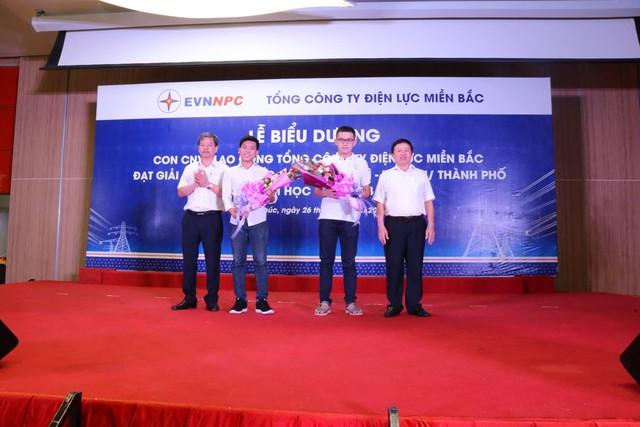Ông Lê Quang Thái - Phó Tổng giám đốc EVNNPC (bên trái) và Ông Nguyễn Văn Tiệp - Chủ tịch công đoàn EVNNPC (bên phải) trao quà tuyên dương cho Nguyễn Hoàng Cường và Lê Bá Hoàng đỗ thủ khoa Đại học Y Hà Nội vì đã có thành tích tốt trong năm học 2017-2018