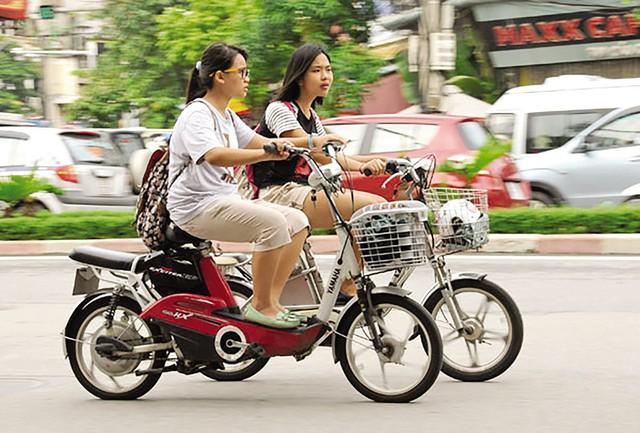 Học sinh đi xe đạp điện dàn hàng ngang không đội mũ bảo hiểm ngày càng xuất hiện nhiều trên đường phố Hà Nội. Ảnh: Hồng Xiêm