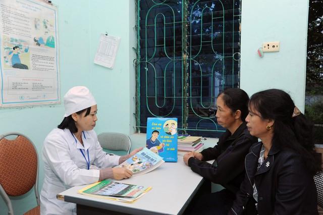 Cán bộ y tế xã Phúc Sơn, huyện Anh Sơn (tỉnh Nghệ An) tuyên truyền kiến thức về dân số và KHHGĐ cho người dân. Ảnh: HUỆ MINH