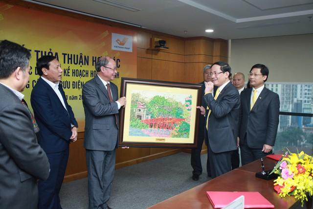 Ông Nguyễn Văn Tân (thứ ba từ trái qua), Phó Tổng cục trưởng phụ trách Tổng cục DS-KHHGĐ và ông Phạm Anh Tuấn (thứ hai từ phải qua), Chủ tịch Hội đồng thành viên Tổng công ty Bưu điện Việt Nam trao quà lưu niệm. Ảnh: VnPost