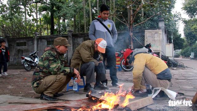 Trên tuyến đường Kim Mã một nhóm người lao động tự do như xe ôm, xe ba gác đang đốt lửa, sưởi ấm - Ảnh: Tuổi trẻ