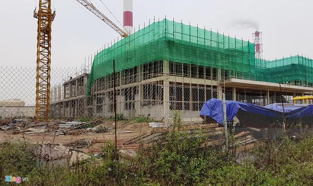 Nhiều hạng mục của dự án nhiệt điện Thái Bình 2 vẫn chưa hoàn thành. Phía ngoài cổng vào chỉ có vài bảo vệ đứng canh. Bên trong không thấy có sự xuất hiện của công nhân, nhiều máy móc và thiết bị được che bạt.