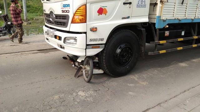 Chiếc xe máy kẹt dưới gầm xe tải.