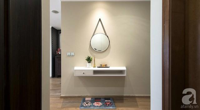 Lối vào nhà không quá rộng nhưng đủ để các kiến trúc sư thiết kế điểm nhấn trên tường, phần diện tích lưu trữ và ánh sáng dịu dàng làm nổi bật những chi tiết nhỏ nhất.