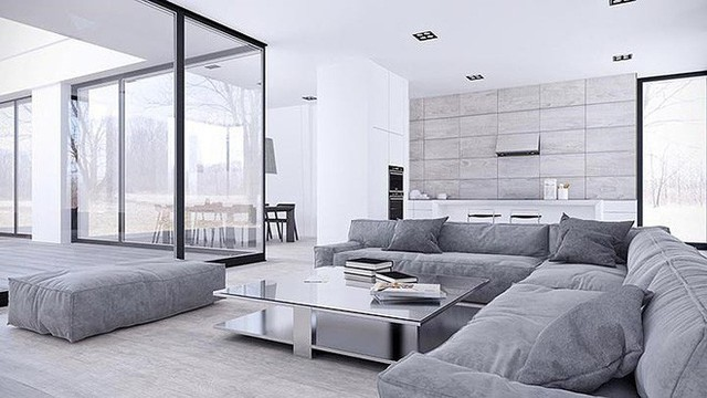 Bộ ghế sofa hiện đại hình chữ L như một vách ngăn, phân chia giữa phòng khách và không gian bếp. Trong ngôi nhà này, phòng ăn hơi hơi lệch về phía một bên nhưng vẫn nhìn thấy đầy đủ thông qua cửa ra vào bằng kính lớn.
